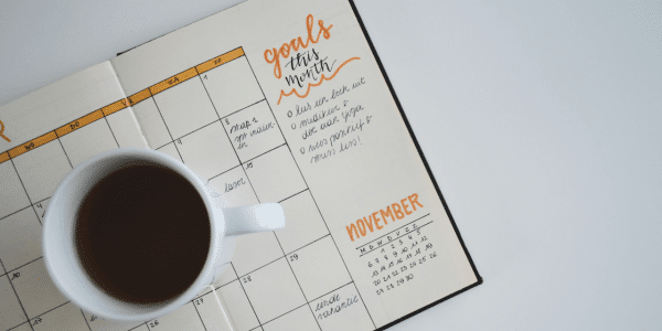 An open diary planner with a calendar spread. 'Goals this month' is written at the top of the page. A cup of coffee sits on top of the open pages