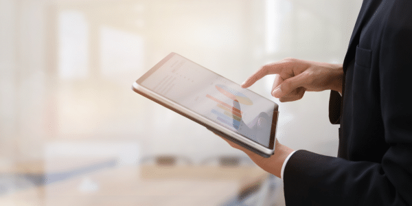 The view of someone's arms holding a tablet, tapping the screen