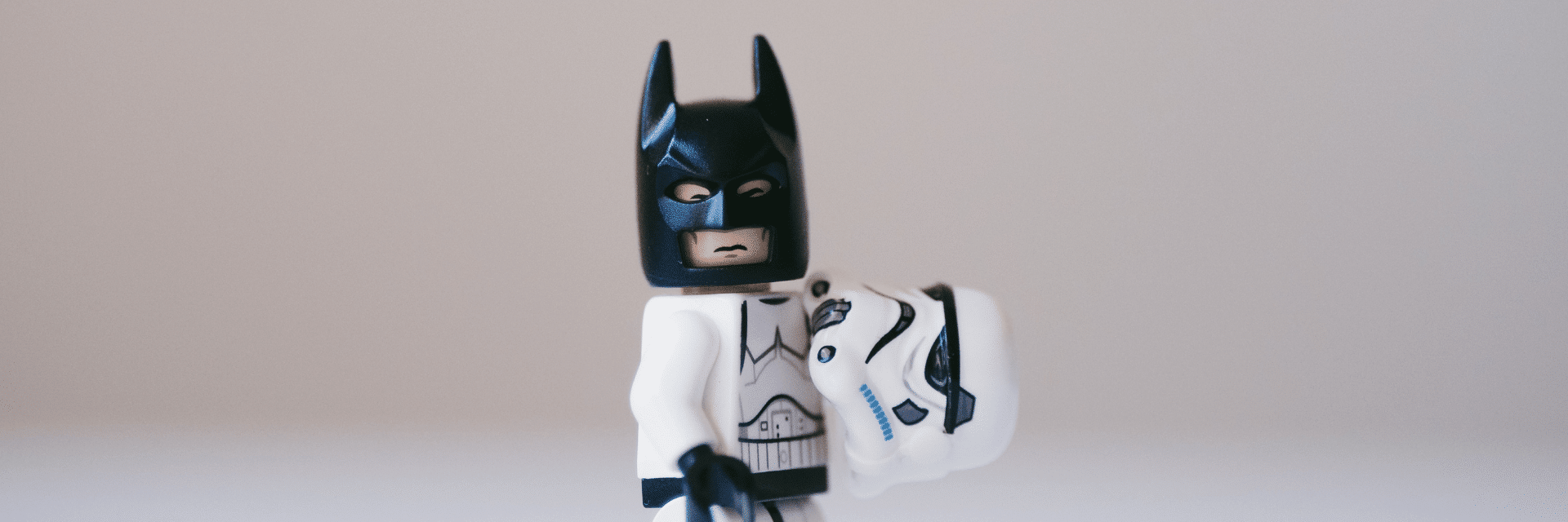 A lego Stormtrooper, holding his helmet in one hand revealing that he's actually Batman.