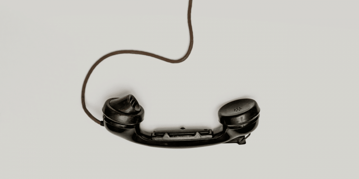 An old fashioned, black phone hanging off the hook