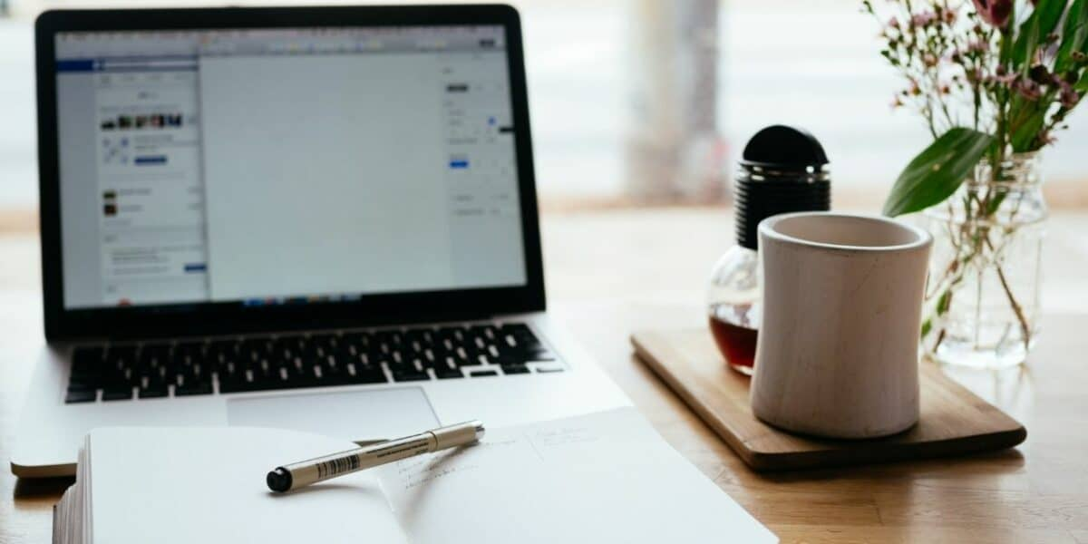 An open laptop showing an organisational program, with a notepad and pen in front of the laptop. There is also a cup of coffee and small plant on the desk.