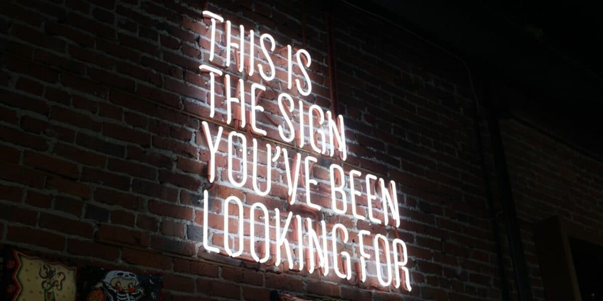 A large pale pink neon light reading 'THIS IS THE SIGN YOU'VE BEEN LOOKING FOR'
