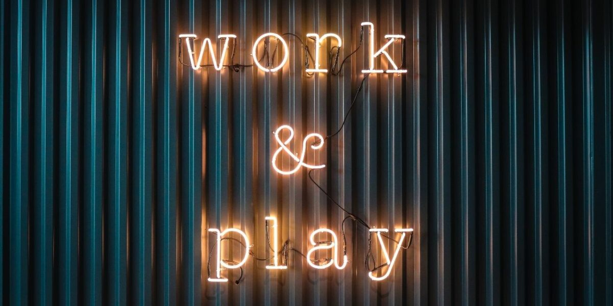 """An orange neon sign against a black industrial background. The sign reads """"WORK & PLAY"""""""