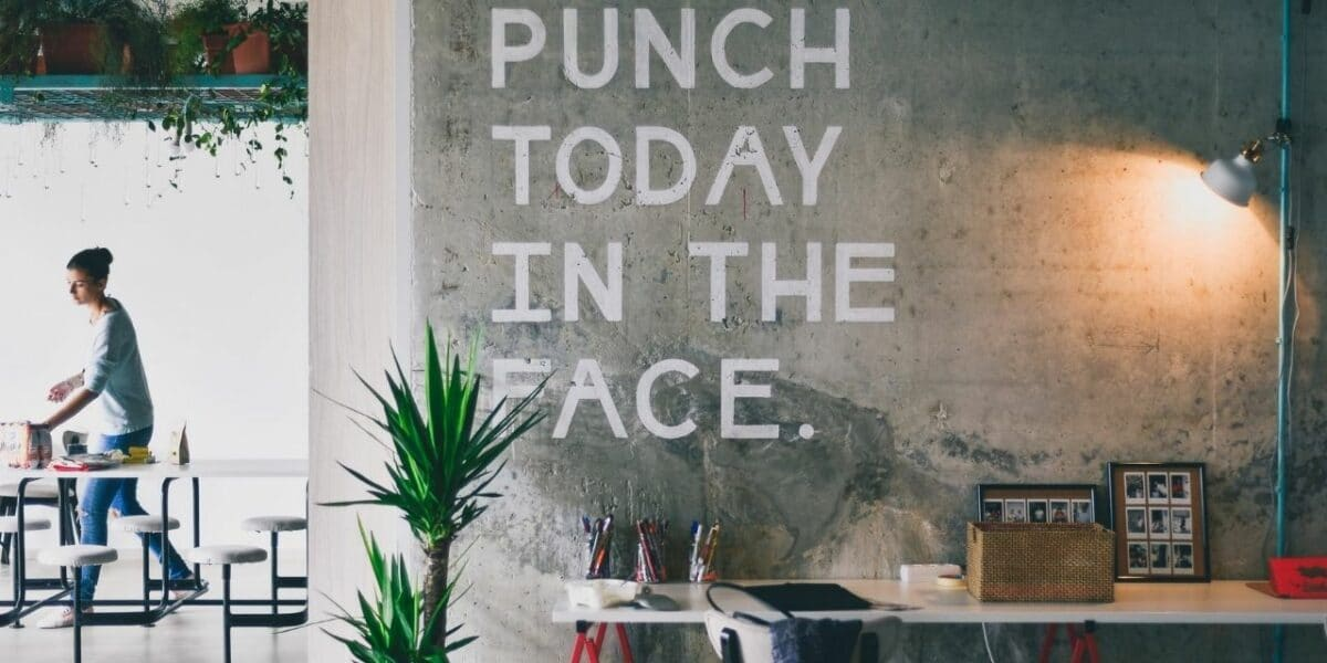 """A busy, modern office setting with lots of plants around. A wall in the foreground has big white text on it, reading """"PUNCH TODAY IN THE FACE"""""""