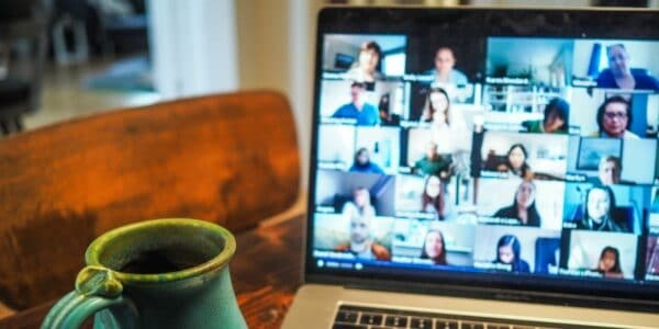 A laptop with a video call full of people slightly out of focus, while a green coffee cup is in focus in the foreground