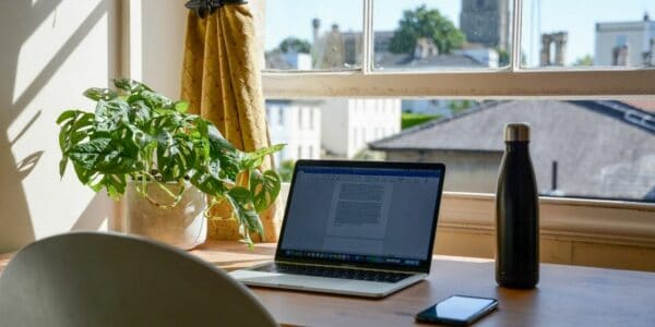 A home desk facing an open window, letting in the sun. The desk has an open laptop, bottle of water, mobile phone and a green houseplant on it.
