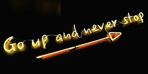 Slanted yellow neon sign reading 'go up and never stop' with an orange neon arrow pointing upwards underneath it
