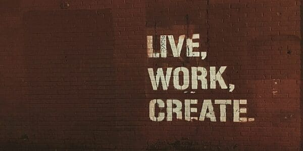 """A red brick wall with white, bold painted words, reading """"LIVE, WORK, CREATE"""""""