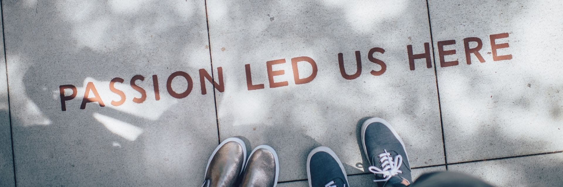 Birds-eye view of the pavement, with 2 people's shoes just in view. There's writing on the pavement reading 'PASSION LEAD US HERE' in red
