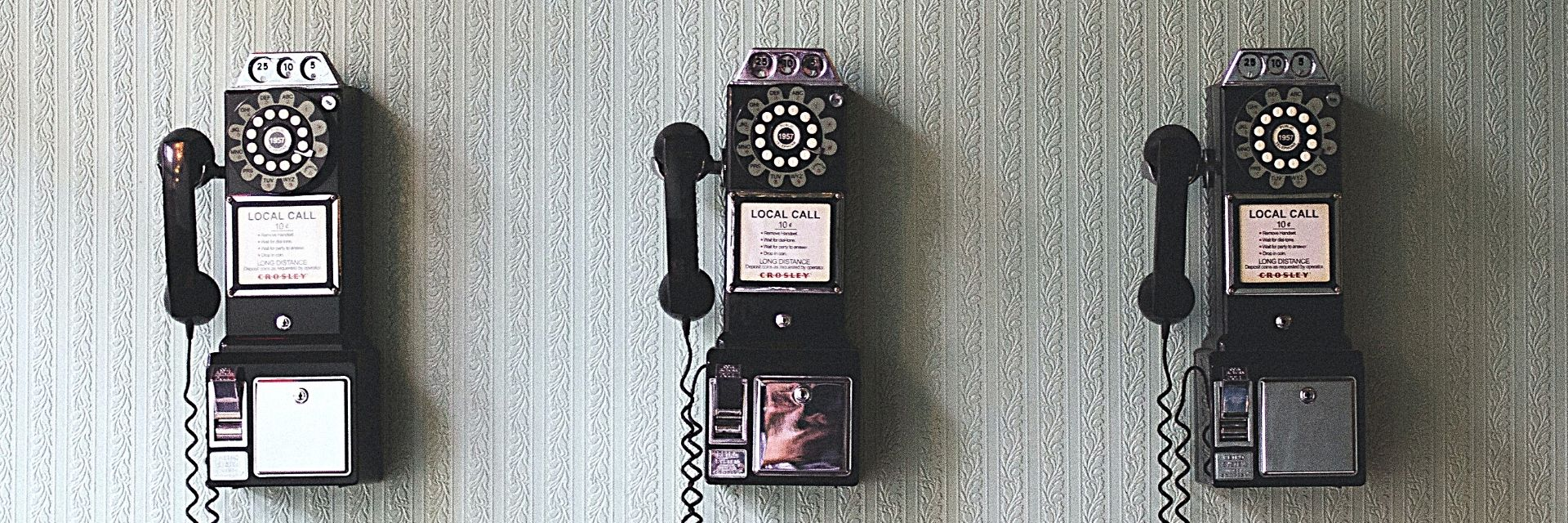 A shot of a wall with 3 old fashioned telephones in a row