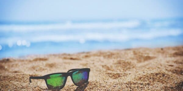Sunglasses on beach sand to represent working remotely