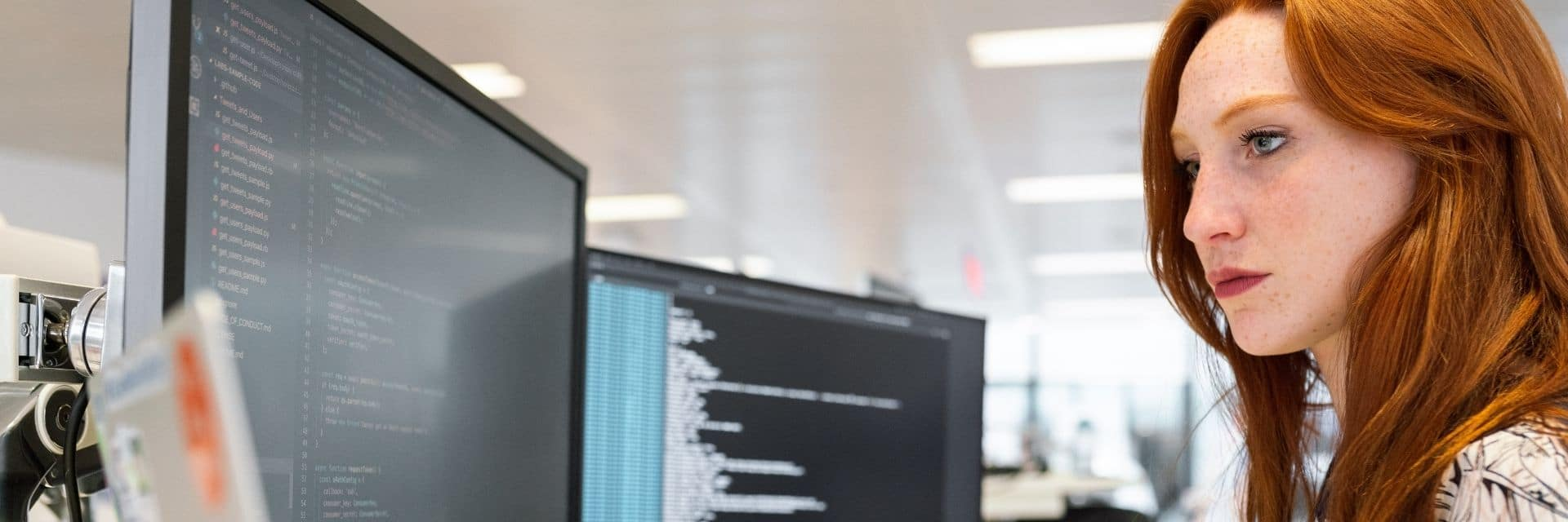 Team member working in front of two computer monitors