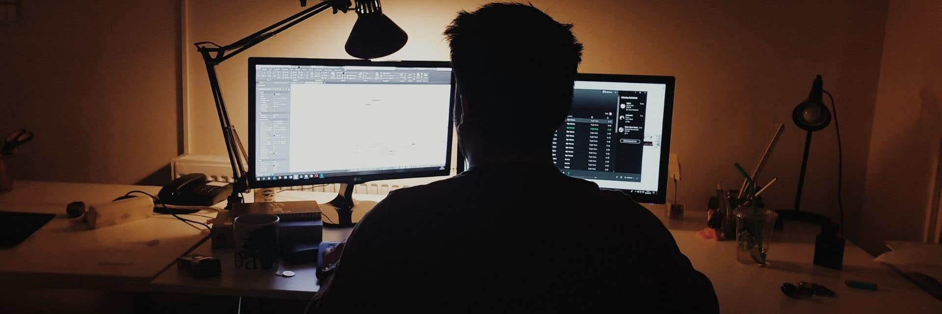 Man stares at two screens while working from home