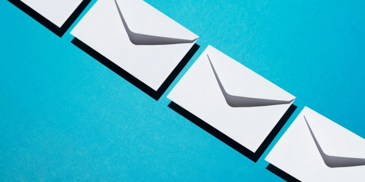 A bright blue background with envelopes lined up in a diagonal line across the image