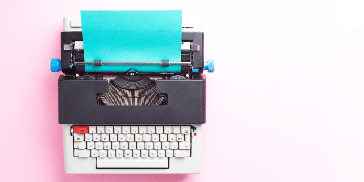 A typewriter on a pink background. The paper inside the typewriter is a bright aqua blue, with no writing on it yet.