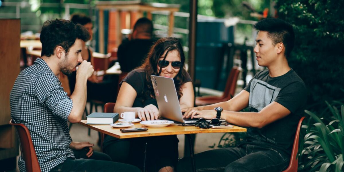 A group of three young adults at a table seated outside. The table has has notepads, coffees and a laptop on it. The three are chatting and laughing.