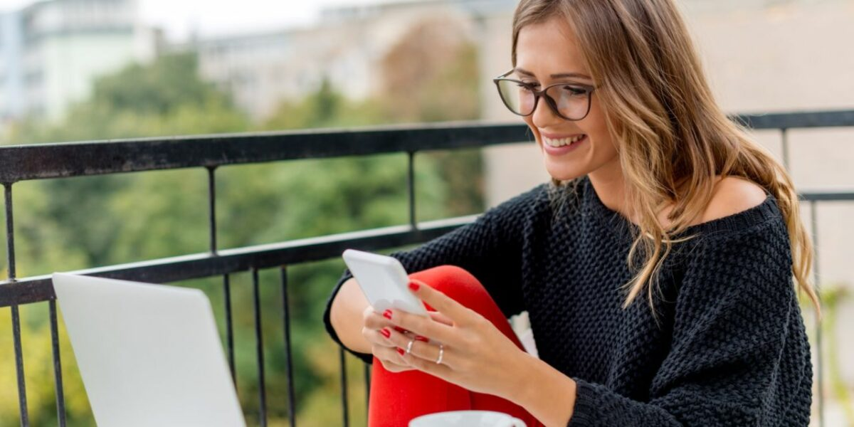 A woman sitting on a balcony smiling at her phone. Her laptop is open in front of her
