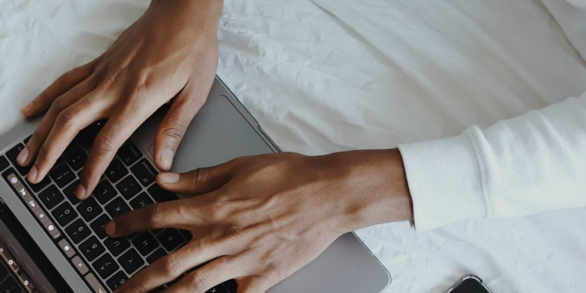 A POC's hands typing on a macbook