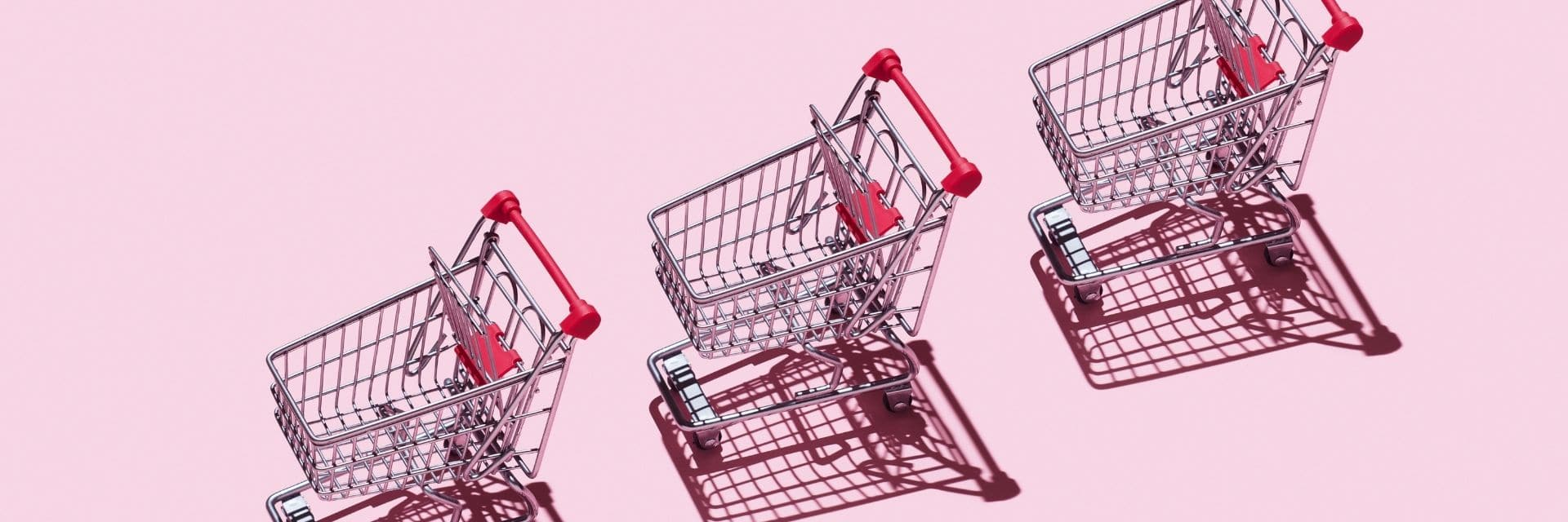A pink background with three shopping carts lined up on top. They have heavy shadow casting next to them but the image is bright.