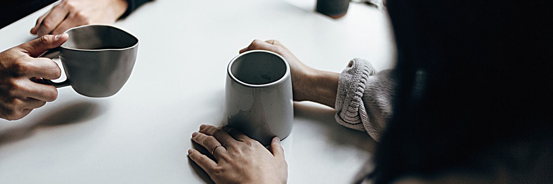 Two people opposite each other, each with a coffee cup in hand. The image only shows their arms and the cups.